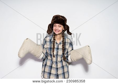 Happy Laughing Russian Girl In A Warm Hat Waits In The Winter, Keeps Warm Felt Boots