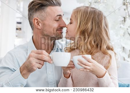Happy Father And Daughter Clinking Tea Cups In Cafe