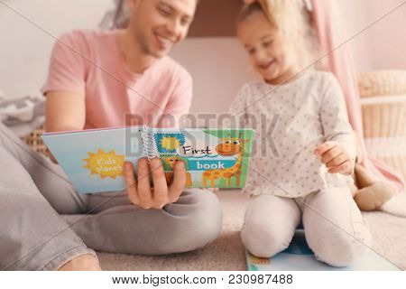 Father with little daughter reading bedtime story near hovel at home