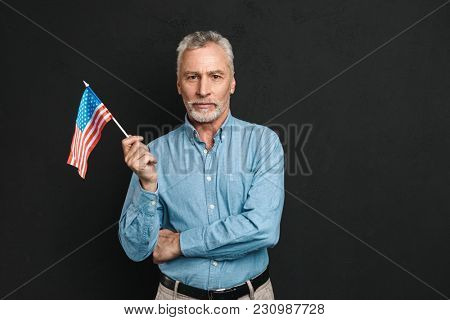 Portrait of businesslike gentleman 50s with grey hair and beard in shirt seriously holding small american flag isolated over black background