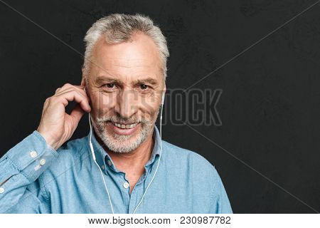 Portrait of handsome pleased mature man 60s with gray hair looking on camera while listening to music via white headphones isolated over black background