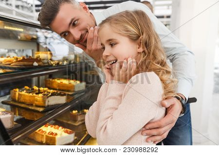 Father And Little Daughter Choosing Cake On Display At Cafe