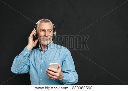 Portrait of unshaved male pensioner 60s with gray hair holding cellphone and listening to music via wireless headphones isolated over black background