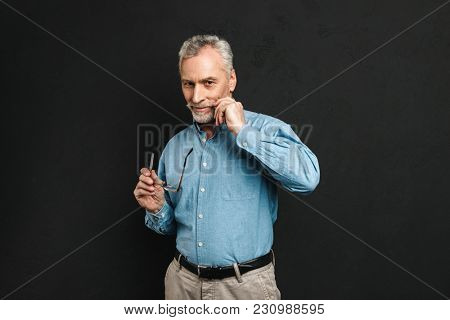 Portrait of caucasian man 60s with grey hair and beard holding glasses while touching his gray mustache isolated over black background