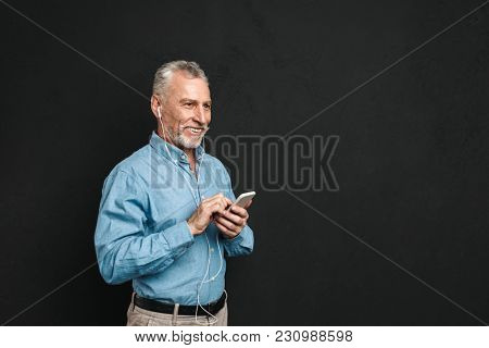 Portrait of cheerful mature man 50s with gray hair typing sms or browsing internet on cell phone isolated over black background