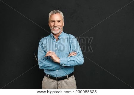 Portrait of caucasian male pensioner 60s with grey hair and beard smiling and holding glasses while standing with arms crossed isolated over black background