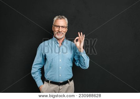 Portrait of businesslike gentleman 50s with grey hair and beard in shirt smiling and gesturing ok sign isolated over black background