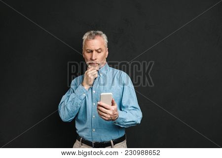 Image of bearded male pensioner 60s with gray hair holding mobile phone with pensive look isolated over black background