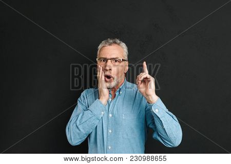 Image of excited retired man 60s with grey hair and beard in shirt shouting in surprise have idea and pointing index finger upward on copyspace isolated over black background