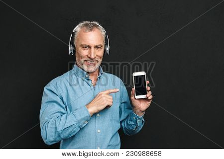 Image of attractive male pensioner 60s with gray hair pointing finger on smartphone while listening to music via wireless headphones isolated over black background