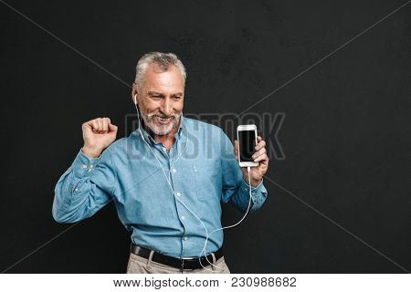 Portrait of happy male pensioner 60s with gray hair dancing while listening to music via white earphones using mobile phone isolated over black background