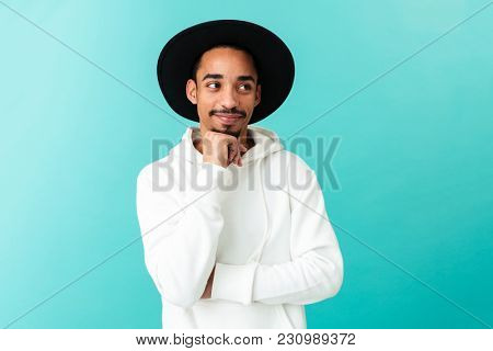 Portrait of a smiling young afro american man in hat looking away with hand on his chin isolated over blue background