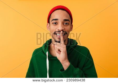 Portrait of a smiling young afro american man in hat showing silence gesture with finger over lips isolated over yellow background