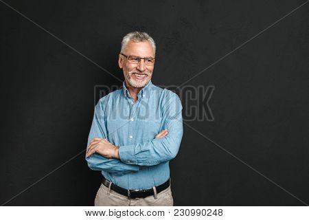 Portrait of caucasian male pensioner 60s with grey hair and beard smiling and looking aside while standing with arms folded isolated over black background