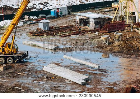 Crane Beam Machinery And Bulldozer On Building Construction Site On Background Of Dirty Ground. Indu