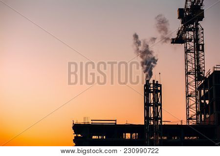 Crane And Building Construction Site With Pipe With Smoke On Background Of Sunset Sky. Industrial La