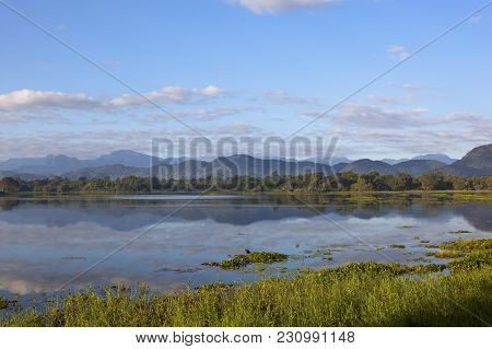 Beautiful Mirror Lake With Woodland And Mountains In Wasgamuwa National Park Under A Blue Sky In Sri