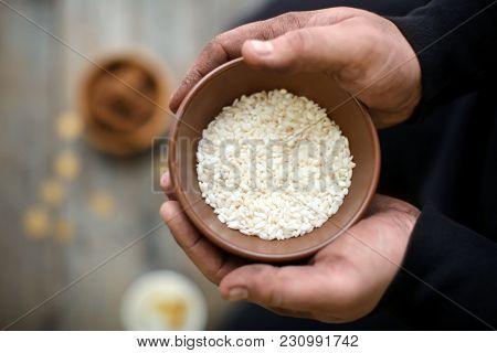 Poor man holding bowl with rice, closeup