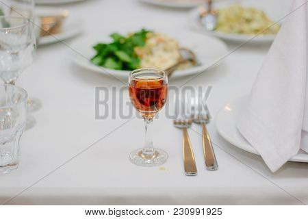 Glass Filled By Red Wine On A Restaurant Table.