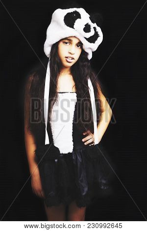 An Adorable Girl In Panda Hat Standing On Black Background.