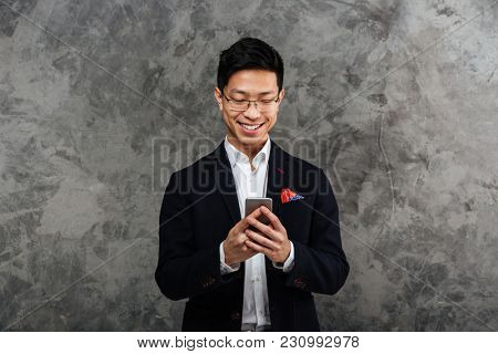 Portrait of a smiling young asian man dressed in suit using mobile phone over gray background