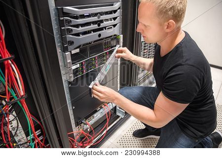 Mid Adult Male It Engineer Checking Computer Server In Datacenter