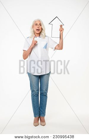 Full length portrait of adorable adult woman 70s with gray hair holding blank speech arrow pointer directing upward isolated over white background
