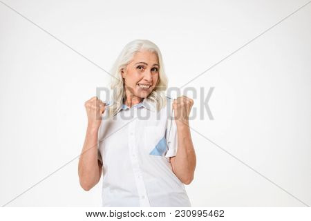 Photo of elder woman with gray hair smiling and clenching fists in happiness isolated over white background