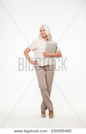 Full length portrait of mature adult woman 60s with gray hair smiling and holding silver laptop in hand isolated over white background