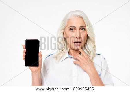 Photo of retired grandmother with long grey hair demonstrating mobile phone with copy space screen isolated over white background