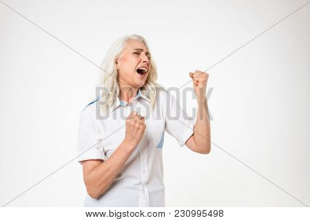 Photo of old woman 60s with gray hair clenching fists and screaming in delight isolated over white background