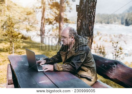 An Adult Partly Bald Game Warden In The Overalls Of Marsh Color Is Sitting Outdoor On The Bench At T