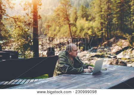 Elderly Man Employer Is Spending His Vacations With Work Outdoors: Sitting With The Laptop At The Wo