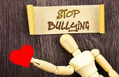 Text sign showing Stop Bullying. Conceptual photo Awareness Problem About Violence Abuse Bully Problem written Sticky Note Love Heart Holding By Sculpture the wooden background. poster