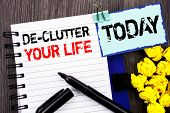Writing text showing  De-Clutter Your Life. Business photo showcasing Free Less Chaos Fresh Clean Routine written notebook book paper the wooden background Today poster