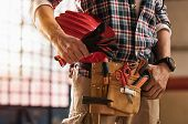 Closeup of bricklayer hands holding hardhat and construction equipment. Detail of mason man hands holding work gloves and wearing tool kit on waist. Handyman with tools belt and artisan equipment. poster