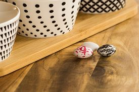 Easter Candy Eggs On Wooden Surface Besides Withe Bowls With Black Pattern Shallow Dof