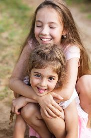 Two Beautiful Little Girls Embracing And Laughing At The Seaside. Happy Kids Outdoors