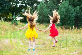 Two Beautiful Little Girls  Jumping And Dancing At Sunny Summer Day. Happy Kids Concept