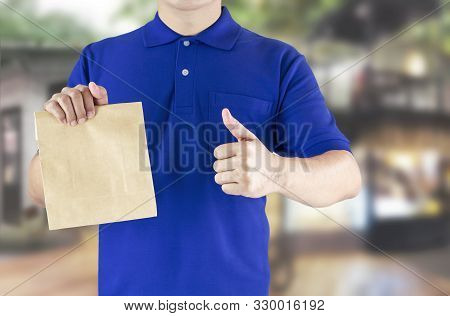 Delivery Man In Blue Uniform And Holding Paper Bag With Delivering Package On Coffee Shop Background