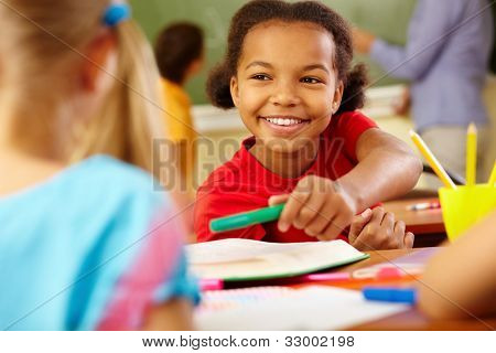 Portrait of cute girl giving crayon to classmate at lesson