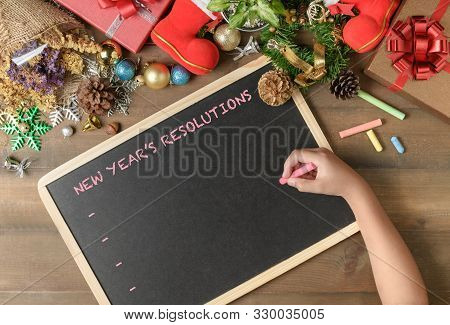 Kid Writing New Year Resolution On Black Board With Decorations And Gift Boxes, New Year And Merry C