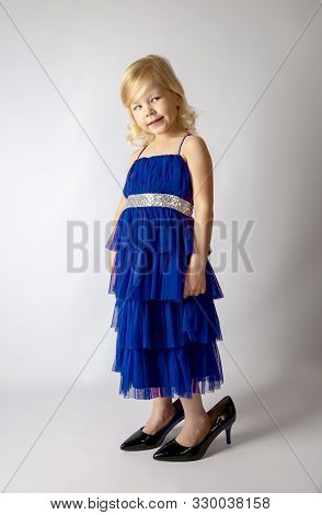 Little Princess Girl In Fashion Blue Dress Wearing Big Mothers Patent Heels Shoes Looks Suspiciously