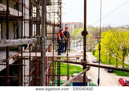 Scaffold Is Placed Against Edifice. Boss Is Oversees From Platform Above Building Site.