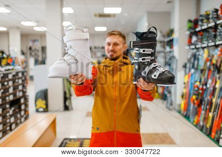Man shows ski or snowboarding boots in sports shop
