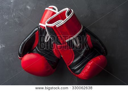 Red Boxing Gloves Hang On The Gray Wall After Training. The Concept Of Professional Boxing. Competit