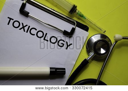 Toxicology On The Document With Yellow Background. Healthcare Or Medical Concept
