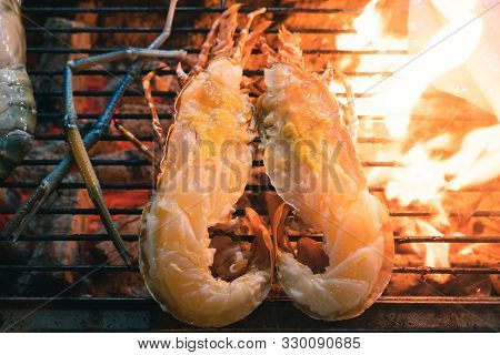 Close Up Of Flame Grilled Lobster, Cut In Half And Grilling On An Outdoors Bbq At A Street Food Mark