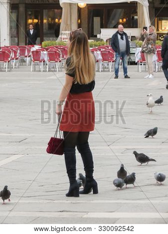 Venice, Italy - Circa March 2018: Unidentified Stylish Young Woman With Pigeons In Piazza San Marco
