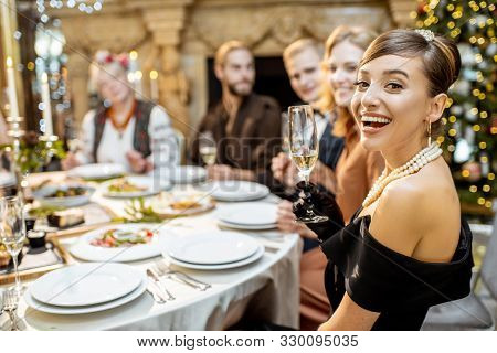 Portrait Of A Well-dressed Woman Sitting During A Festive Dinner With Friends On New Years Eve At Th